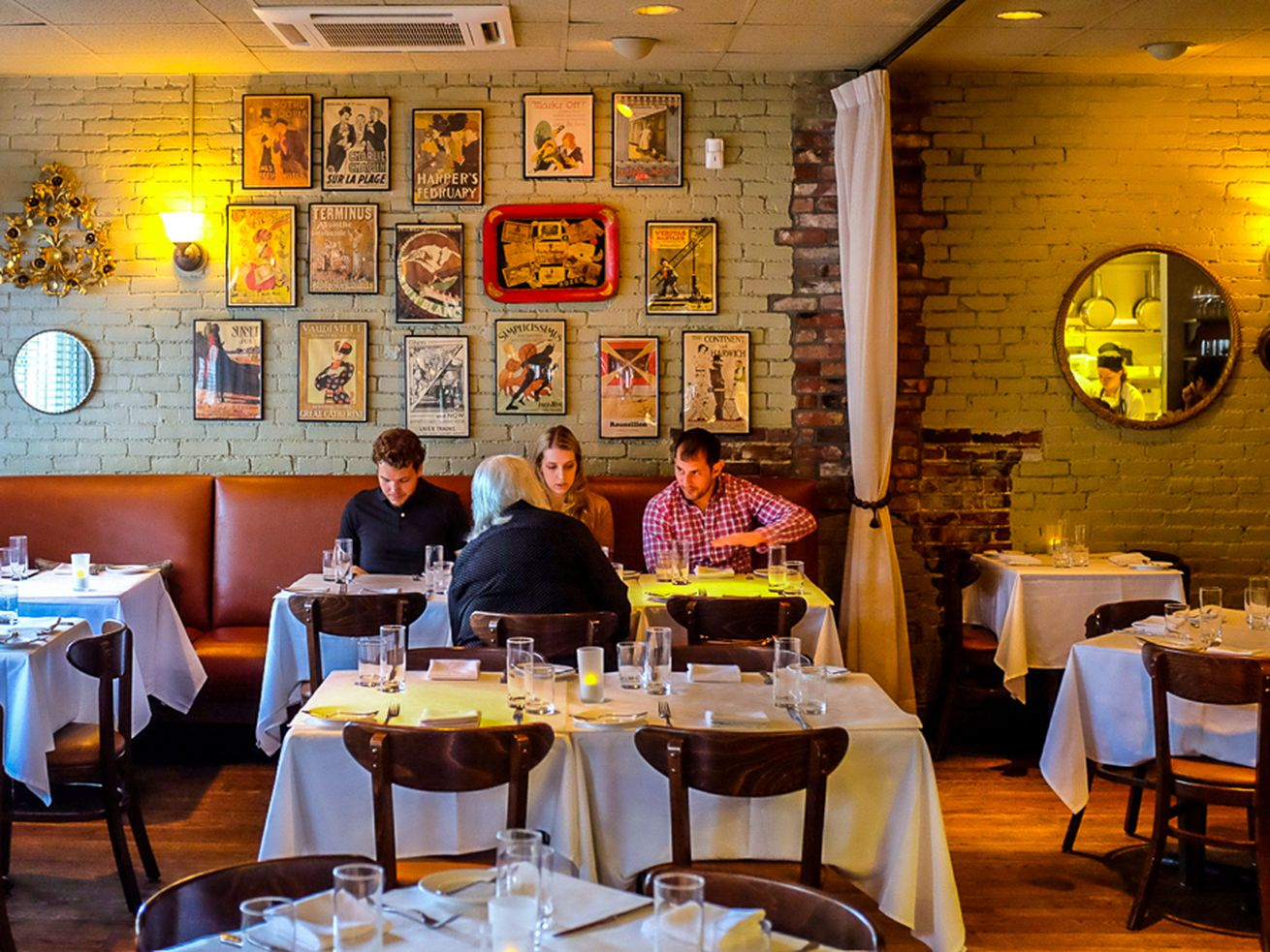 The inside of a sort of casual, bistro-like restaurant with white brick walls. Four young professionals sit at a white tablecloth-covered table.