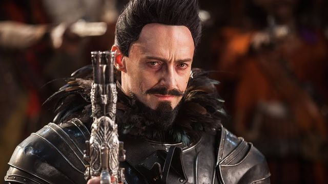 hugh jackman in pan with a gun and a black goatee