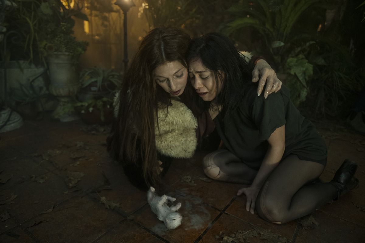 Lisa N. Nova and the witch Boro kneel over a kitten Lisa has just barfed up in Netflix's Brand New Cherry Flavor.