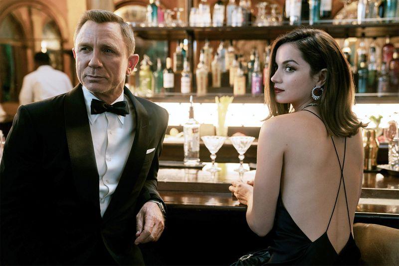 James Bond and Paloma at a bar in formalwear.