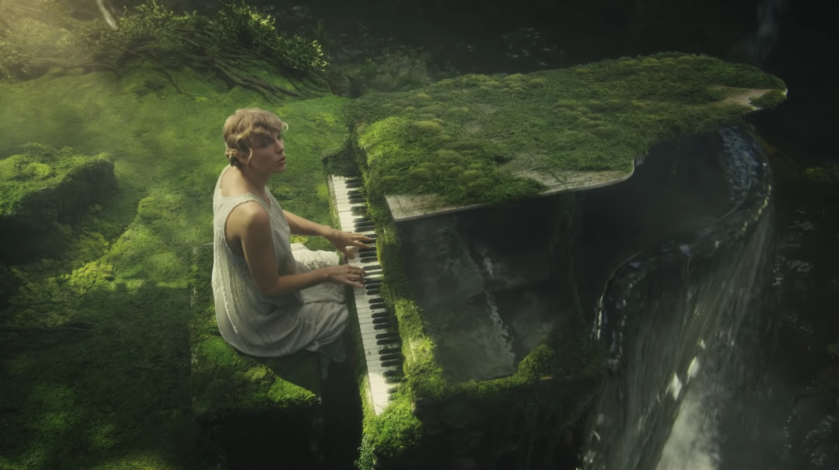 "Taylor Swift sits at her piano in a forest in the music video for ""Cardigan."""