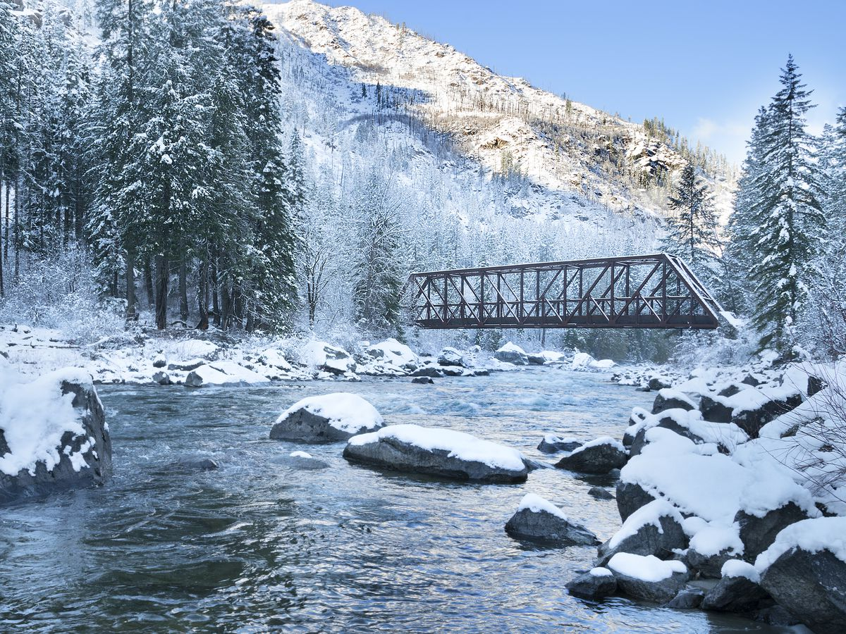 A railroad bridge over a rocky river on a snowy day, with evergreen trees on either side and a mountain behind.