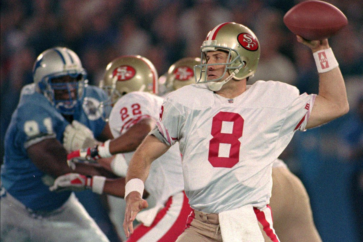 San Francisco 49ers quartertback Steve Young reaches back to throw a pass to receiver John Taylor.