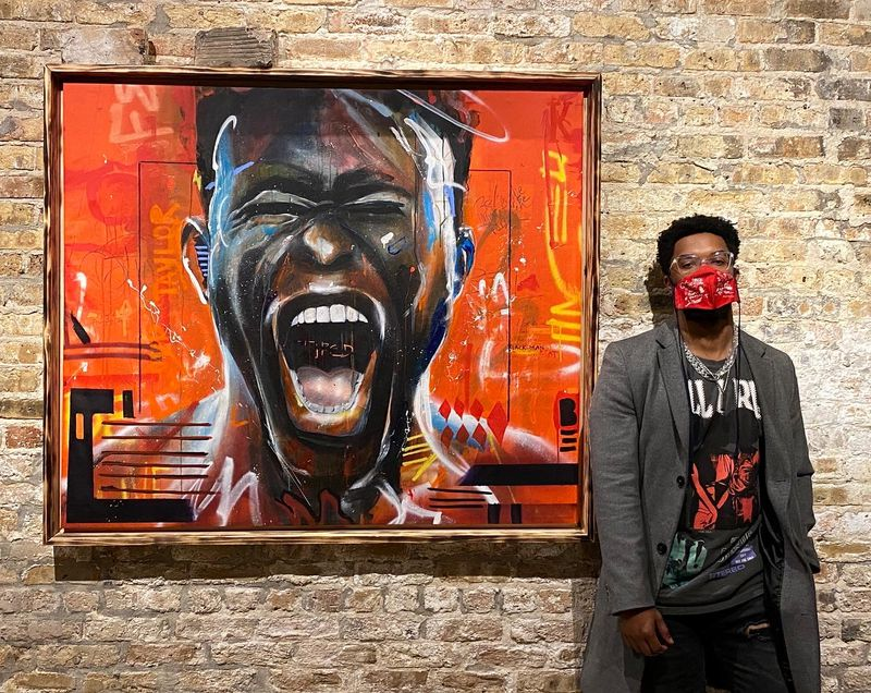 Dwight White II in front of one his paintings.