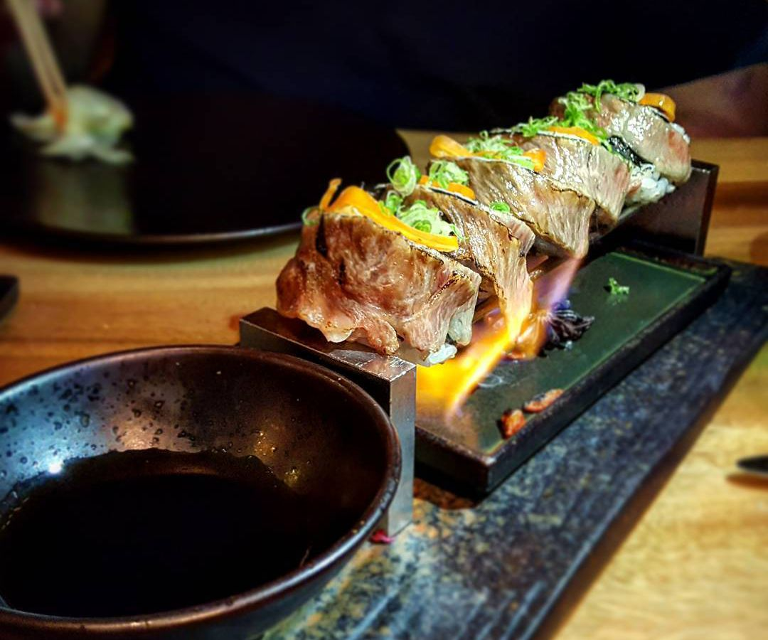 Slices of wagyu beef above a flame with a small dark bowl filled with dipping sauce