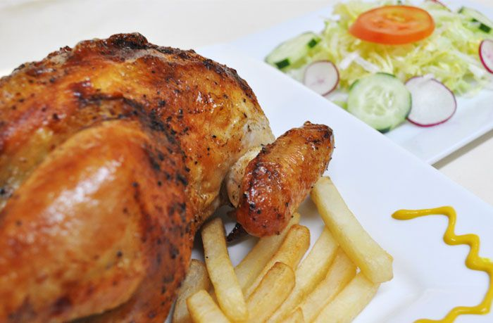 Peruvian-style rotisserie chicken on a white plate with fries. A plate with a simple salad is visible in the background.