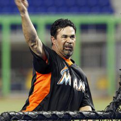Miami Marlins manager Ozzie Guillen pitches during batting practice before a spring training baseball game against the New York Yankees in Miami, Monday, April 2, 2012.