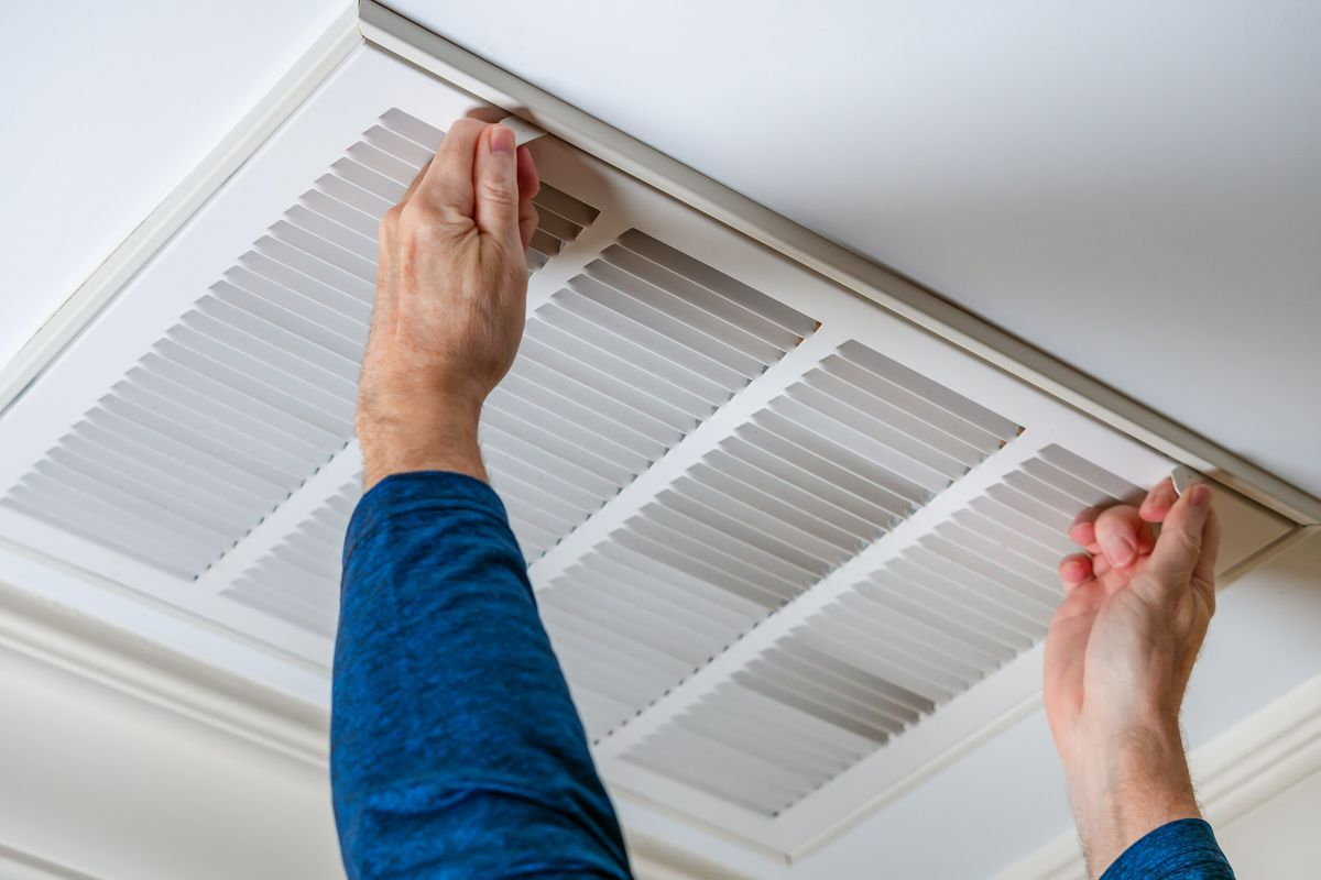 Close-up on a person opening an air vent in the ceiling.
