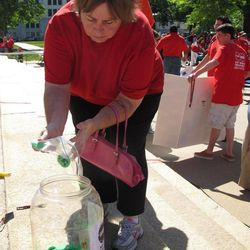 """Mary Moore, of Wichita, Kan., dumps plastic chips into a plastic container on the south steps of the Statehouse  during a rally to protest Gov. Sam Brownback's plan to overhaul Medicaid, Wednesday, April 25, 2012, in Topeka, Kan. The container of chips are in keeping with one slogan of critics of the plan, who contend it's """"not worth the gamble."""""""