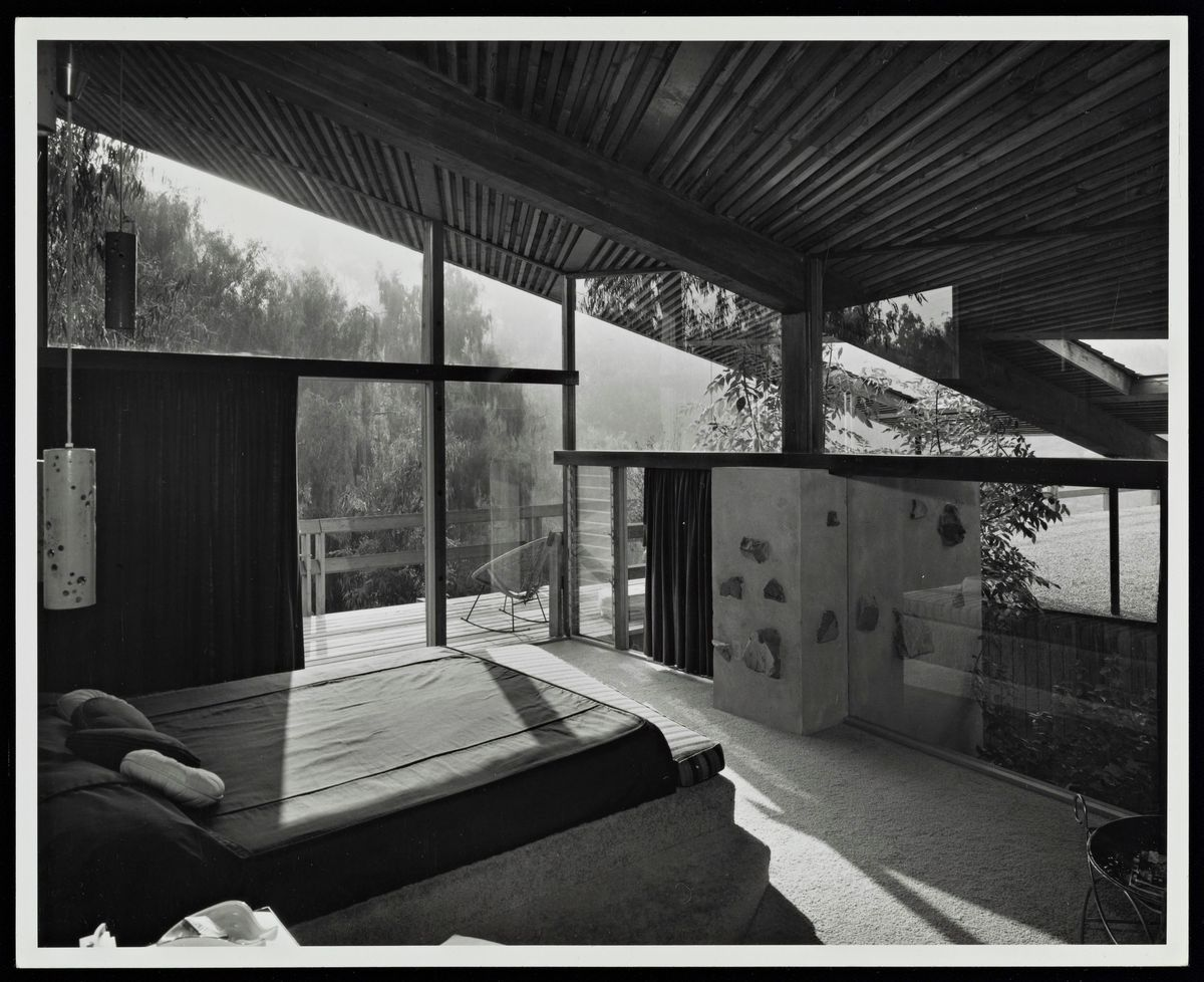 Black and white photo showing sloped ceilings over a bedroom with glass walls.