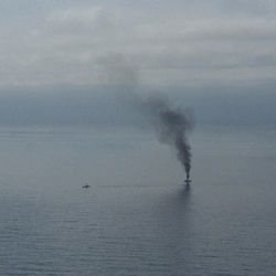 A giant plume of smoke rises from a derelict Japanese ship after it was hit by canon fire by a U.S. Coast Guard cutter on Thursday, April 5, 2012, in the Gulf of Alaska. The Coast Guard decided to sink the ship dislodged by last year's tsunami because it was a threat to maritime traffic and could have an environmental impact if it grounded.