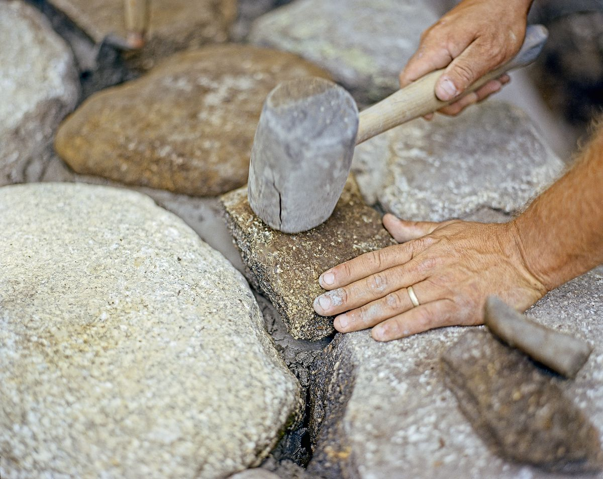Man Tamps Down Stone Into Mortar With Mallet