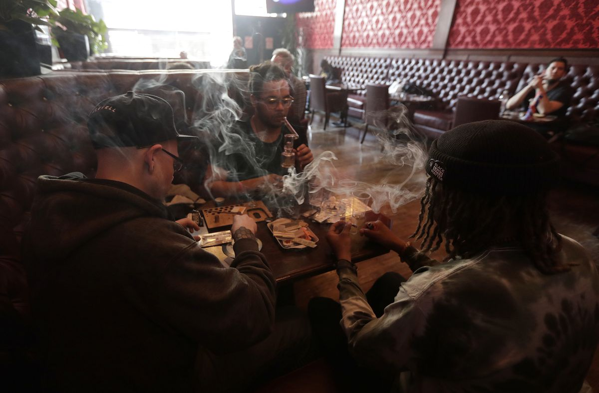 In this March 1, 2018 photo, Rick Thompson, (clockwise from left), Keith Baskerville and Xavier Baskerville smoke marijuana while sitting in a booth in the smoking lounge at Barbary Coast Dispensary in San Francisco. San Francisco plans to issue more perm