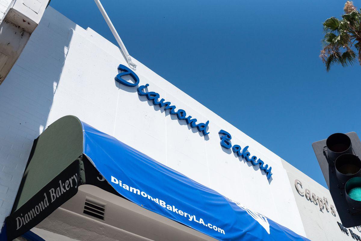 Một góc nhìn nghiêng nhìn lên một tòa nhà màu trắng với các chữ cái màu xanh lam và bầu trời bên kia.