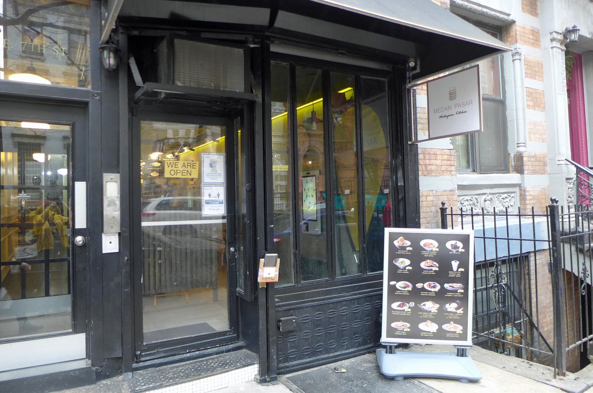 A black storefront with a menu board in front.