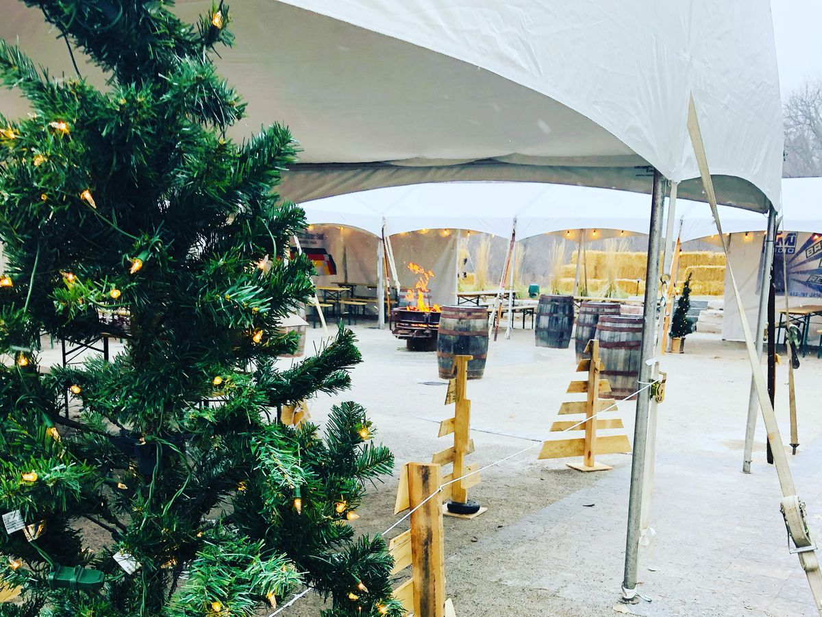 An open side tent is visible behind a Christmas tree with a fire pit roaring