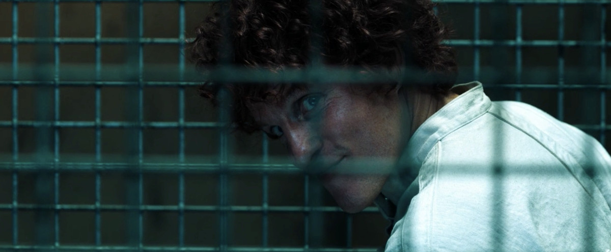 Woody Harrelson as the serial killer looks through jail bars and wears a silly-looking red curly wig (that is meant to be his hair)