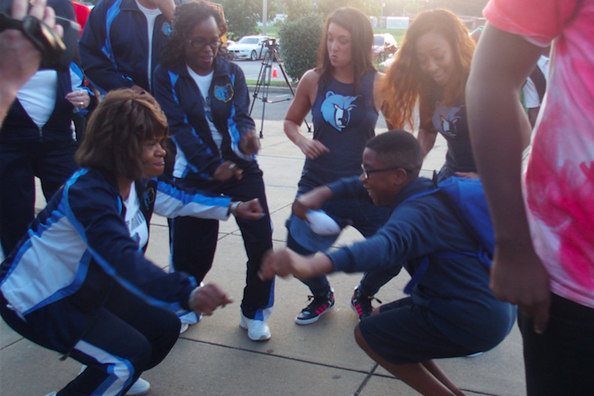 A student at A. Maceo Walker Middle School and a volunteer with the Memphis Grizzlies  celebrate the start of a school attendance campaign through a partnership of the NBA team, Shelby County Schools and Seeding Success.