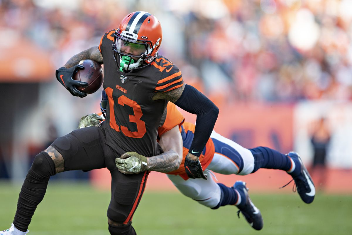 Odell Beckham Jr. of the Cleveland Browns runs the ball and is grabbed by Justin Simmons of the Denver Broncos at Broncos Stadium at Mile High on November 3, 2019 in Denver, Colorado.