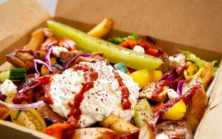 Doner kebab and veggies served over a bed of fries.