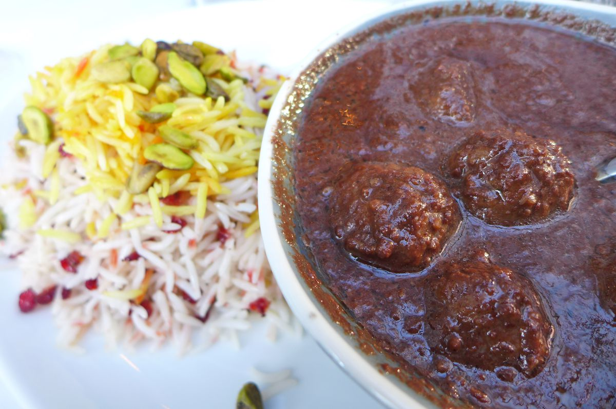 A bowl with three meatballs in a dark red and grainy sauce, with colorful rice in the background.