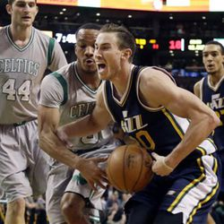 Utah Jazz forward Gordon Hayward, second from right, drives against Boston Celtics guard Avery Bradley (0) as Celtics center Tyler Zeller (44) and Jazz center Rudy Gobert (27) look on during the first half of an NBA basketball game in Boston, Wednesday, March 4, 2015. (AP Photo/Elise Amendola)