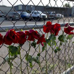 Flowers hang on the fence outside the Granite Mountain Hot Shot Crew fire station, Monday, July 1, 2013, in Prescott, Ariz. An out-of-control blaze overtook the elite group of firefighters trained to battle the fiercest wildfires, killing 19 members as they tried to protect themselves from the flames under fire-resistant shields. The disaster Sunday afternoon all but wiped out the 20-member Hotshot fire crew leaving the city's fire department reeling. (AP Photo/Julie Jacobson)