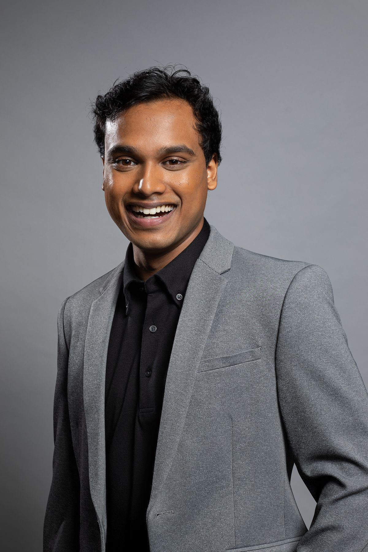Jimmy Mondal, standing against a gray background smiling, wearing a gray suit jacket over a black dress shirt