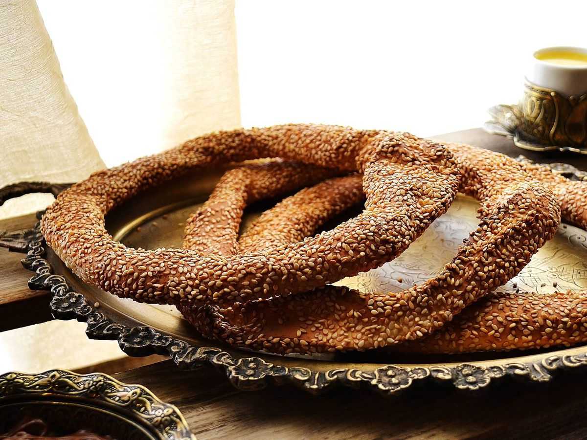 Three thin bagels topped with sesame seeds on a metal platter by a shaded window