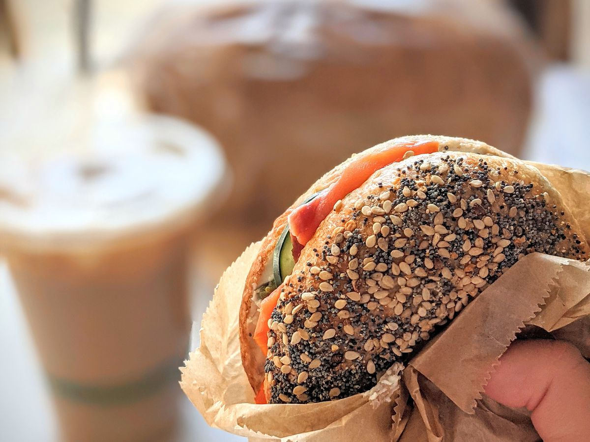 A hand clutches a poppyseed covered bagel wrapped with brown wax paper. Inside smoked salmon and a red onion are spilling out.