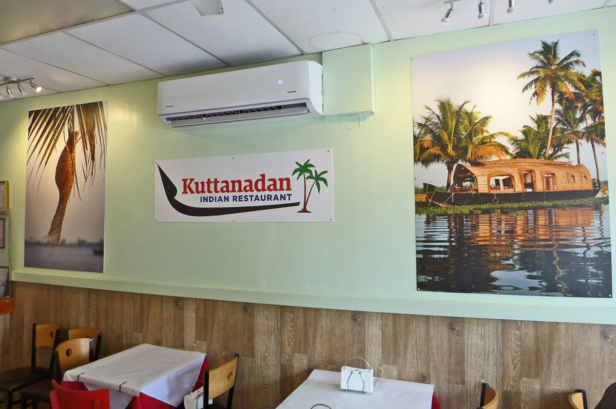 A restaurant interior with a poster of a boat and a coconut tree.