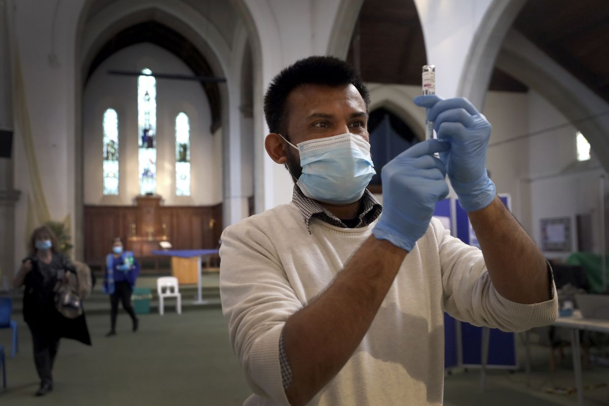Pharmacist Rajan Shah prepares a syringe of the AstraZeneca vaccine at St John's Church, in Ealing, London, Tuesday, March 16, 2021.
