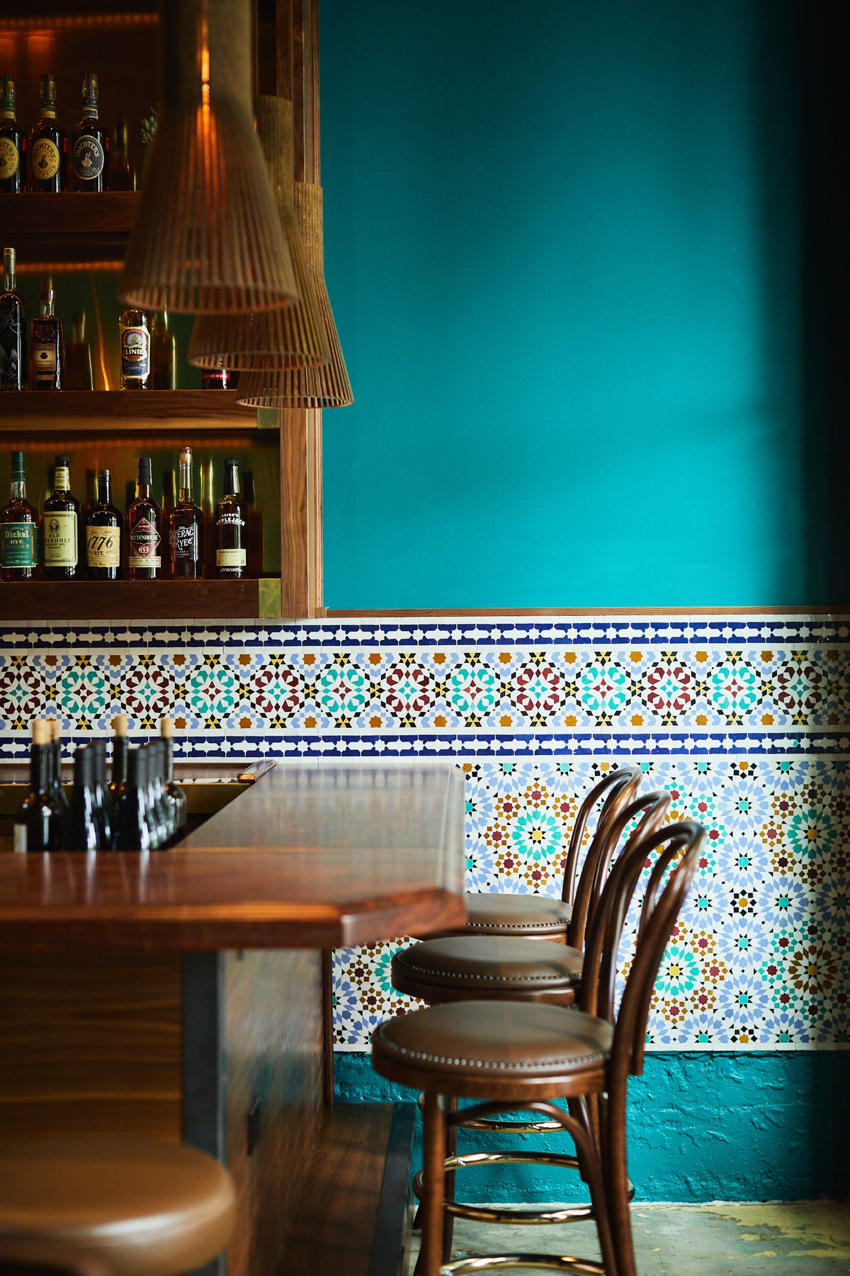 A view of the bar, with wooden chairs and a blue wall trimmed with an ornate design.