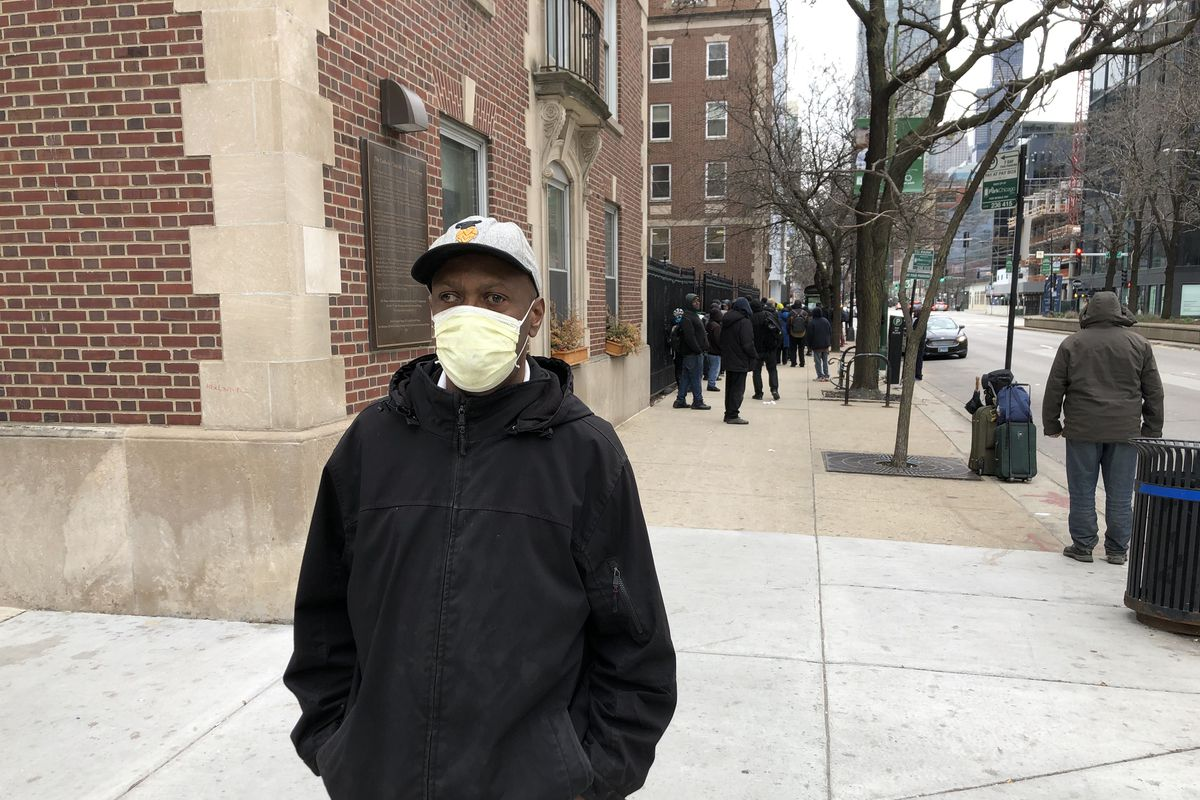 Mark Anderson, who lost his part-time restaurant job in the pandemic and sleeps most nights on the CTA, waits outside Catholic Charities to pick up his free hot meal