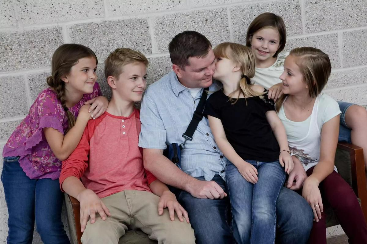 Evie Clair and her siblings are photographed with their father.