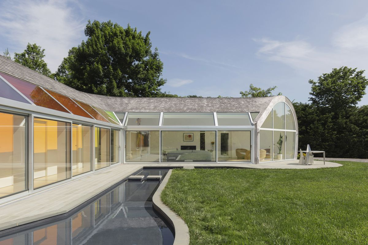 Exterior of house with reflecting pool and green yard.