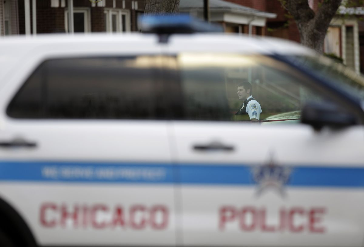A police officer, glimpsed through the window of his cruiser, at a Chicago crime scene in 2016.