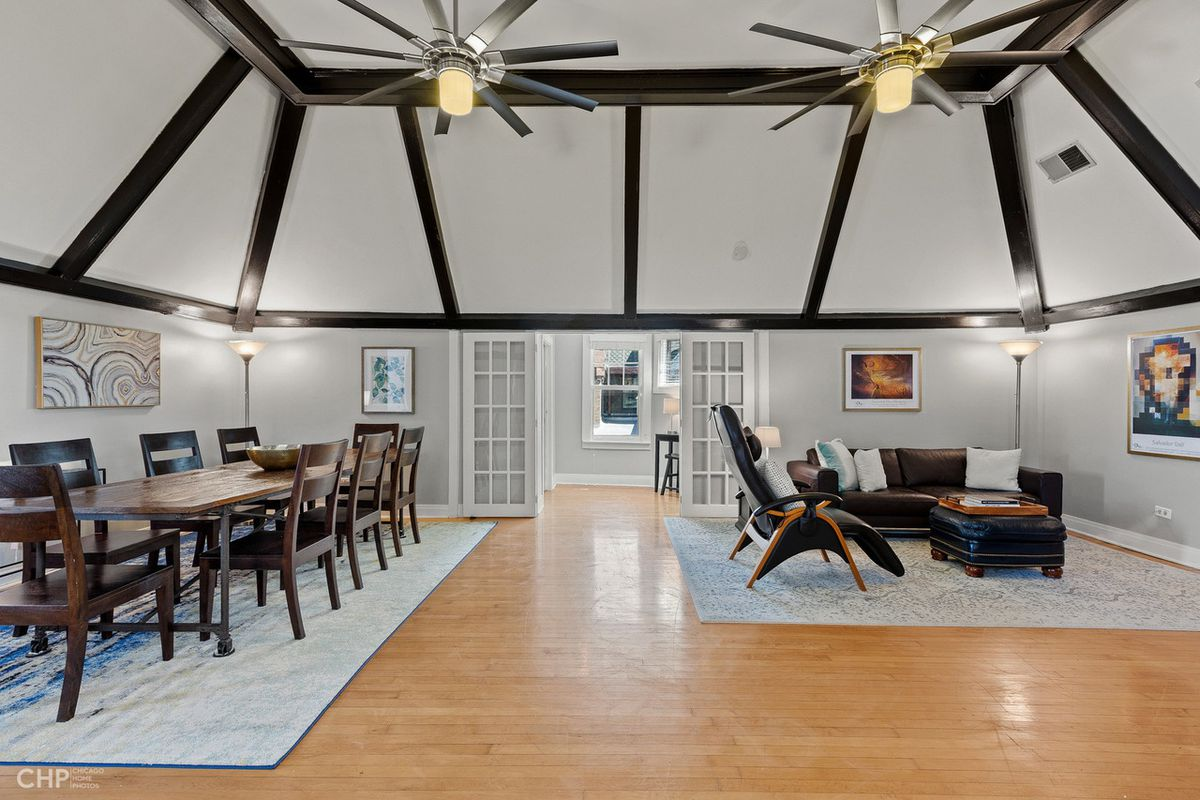 The grand parlor living space has a vaulted ceiling with wood beams and room for a massive dining table.