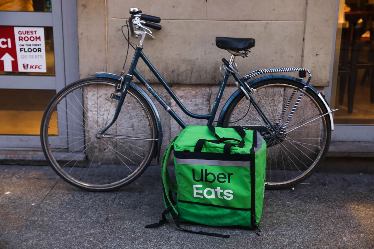 A food delivery bag is placed against a standing bicycle that is reclining against a wall.