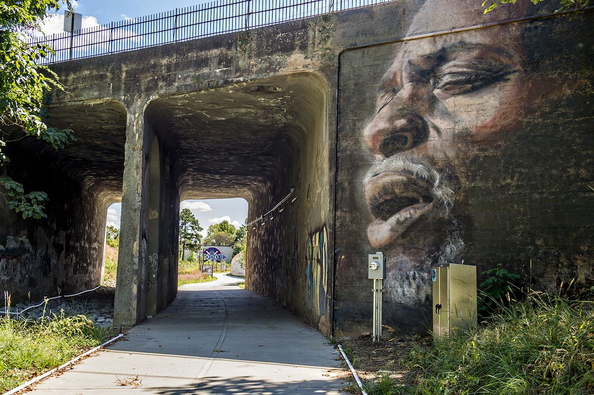 A tunnel with a mural of a man singing.