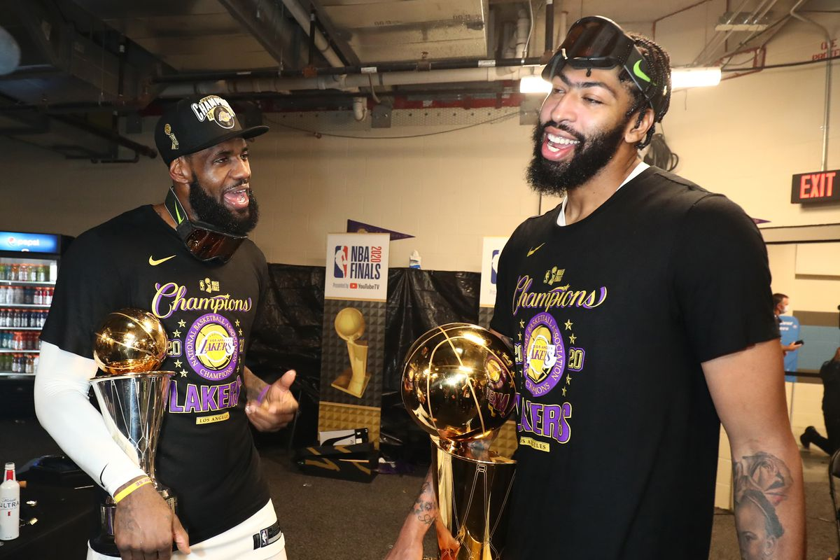 LeBron James and Anthony Davis of the Los Angeles Lakers holds the Larry O'Brien Trophy and The Bill Russell NBA Finals MVP Award in the locker room after winning Game Six of the NBA Finals on October 11, 2020 at AdventHealth Arena in Orlando, Florida.
