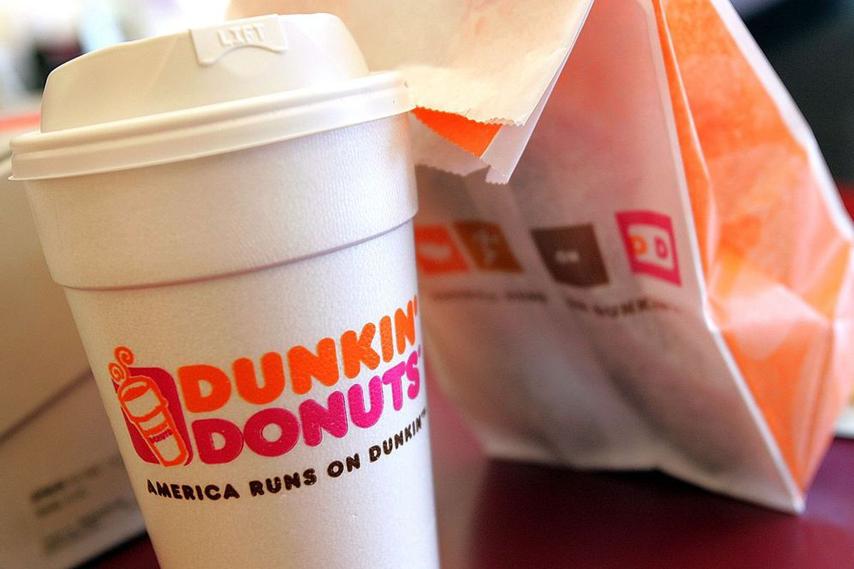 A cup of Dunkin' Donuts coffee and a donut bag sit on a counter