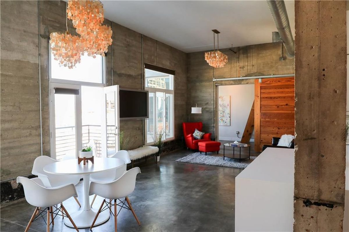 Loft-style condo living room interior with concrete walls, modern decor and furnishing