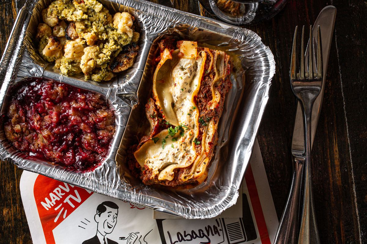An old-school aluminum TV tray with three compartments: lasagna, veggies, and a berry sprinkle