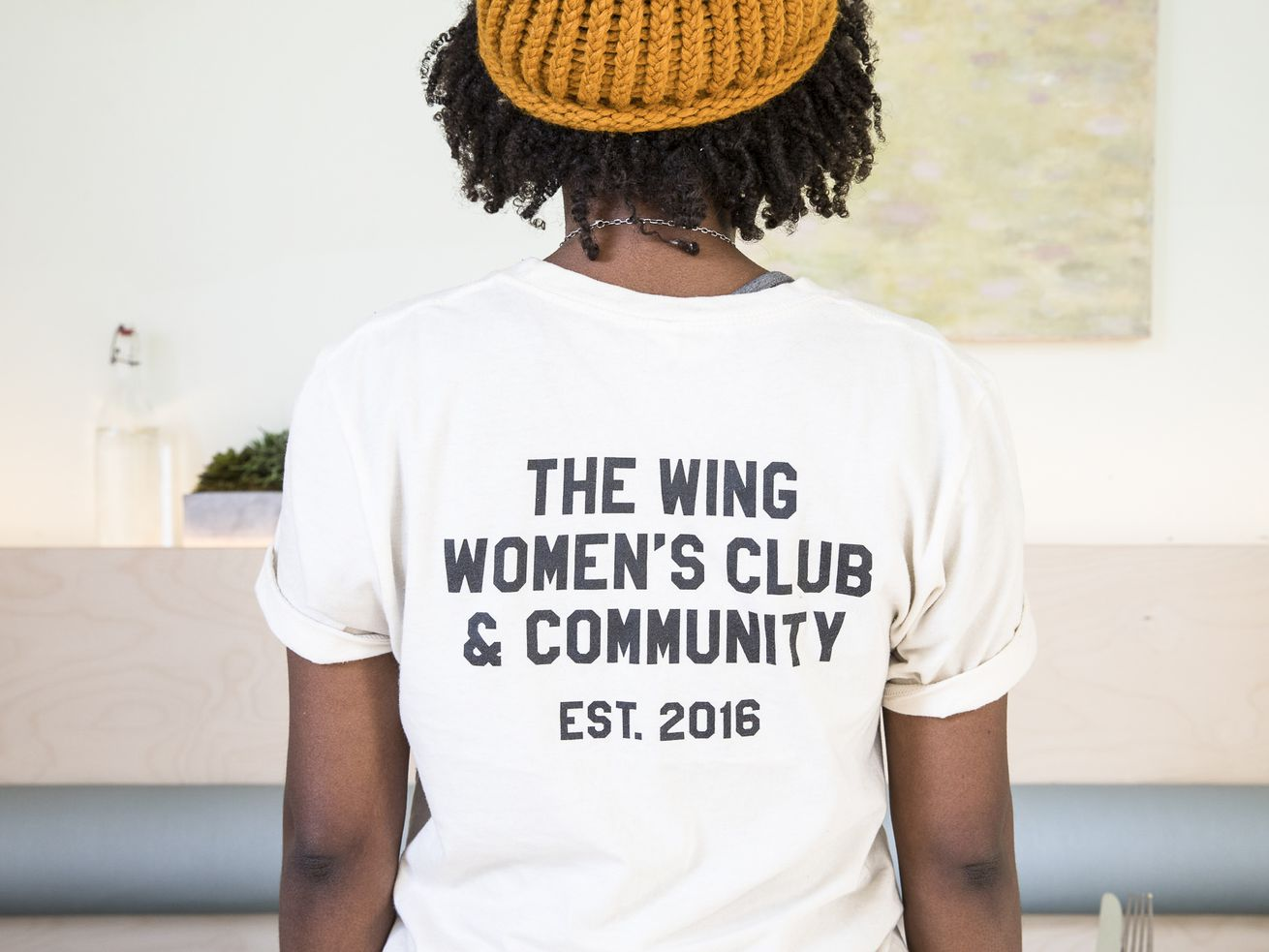 "A woman in a t-shirt that reads ""The Wing women's club & community, established 2016."""