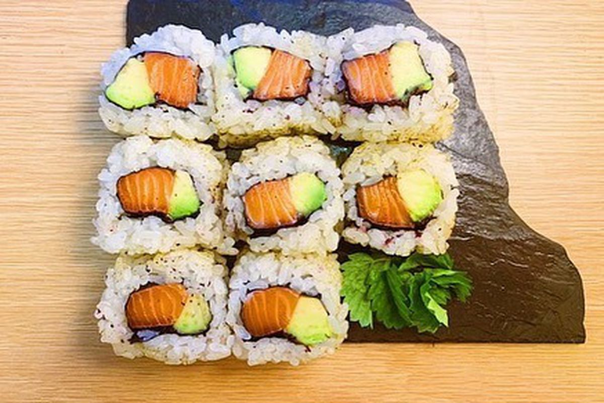 Eight sushi rolls wrapped in rice with the fish and avocado visible inside