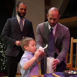 Jesse Milner-Barraza, 4, lights a candle during the wedding ceremony of his parents, Matt Barraza and Tony Milner, at the United Church of Christ in Holladay on Friday, Dec. 20, 2013. Barraza and Milner have been together for eleven years and have been raising their son Jesse since the day he was born.