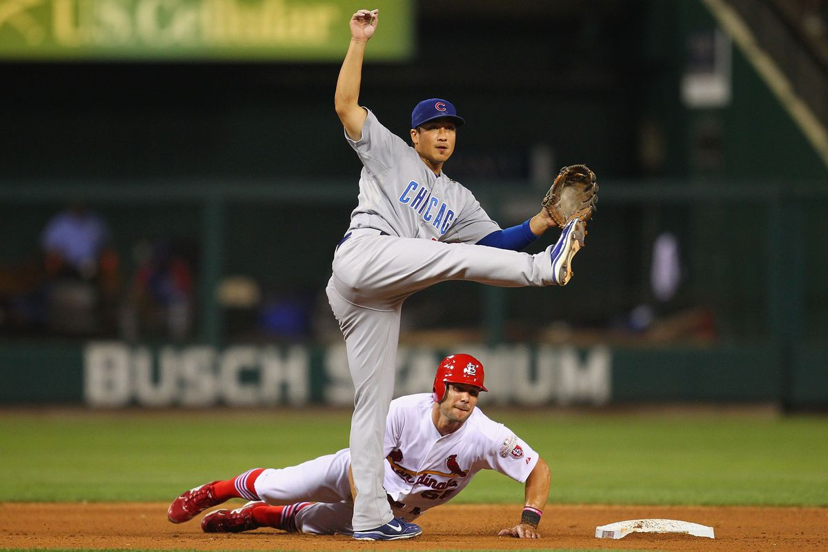 Write your own caption: Skip Schumaker of the St. Louis Cardinals breaks up a double play against Darwin Barney of the Chicago Cubs at Busch Stadium in St. Louis, Missouri.  (Photo by Dilip Vishwanat/Getty Images)