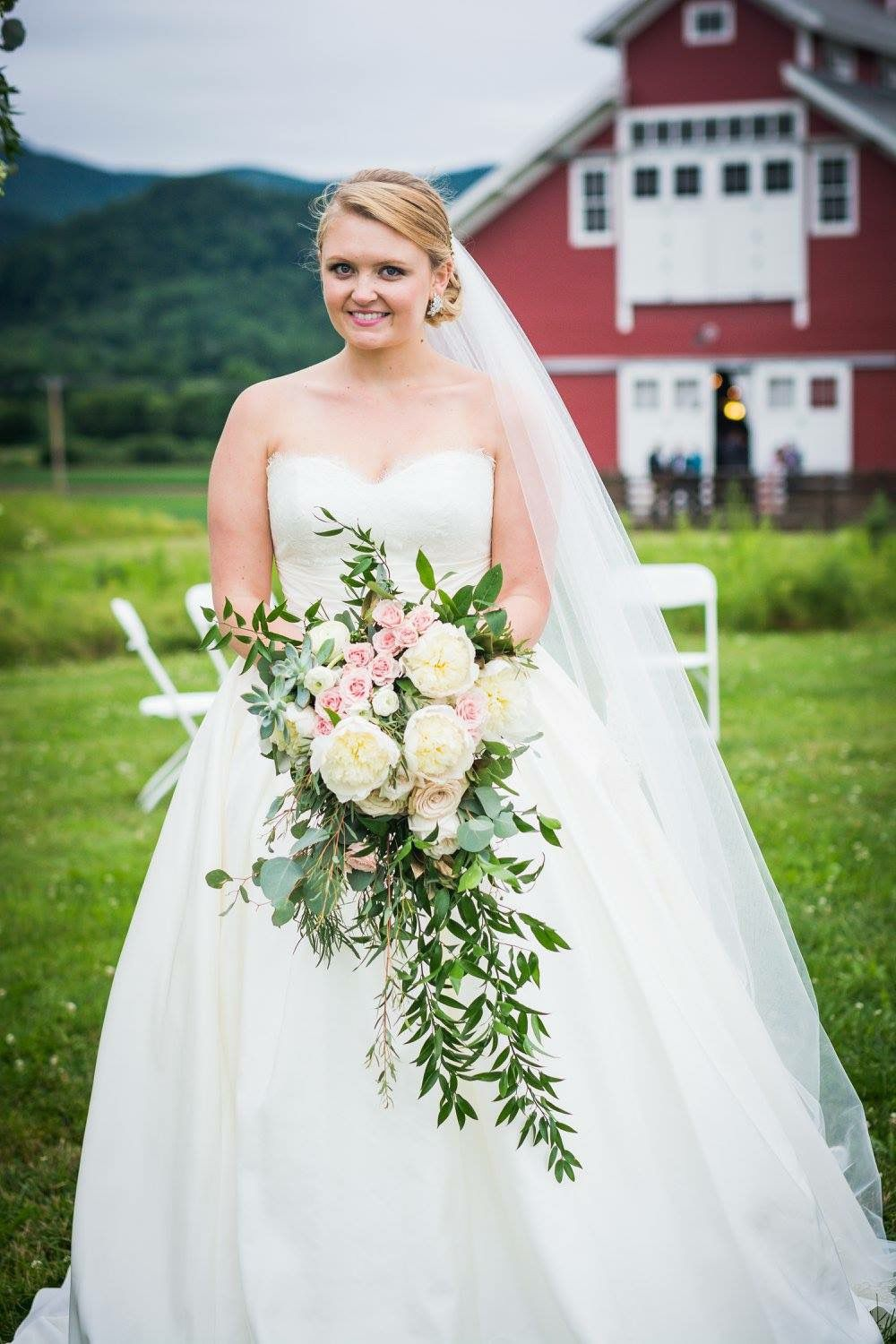 A bride holding a bouquet, standing in a field in her wedding dress.