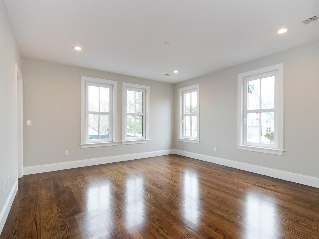 An empty bedroom with four windows, two each on walls that meet at a corner.